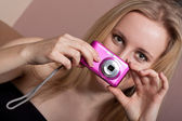 Pretty young blond girl with a photo camera — Stock Photo