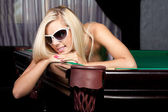 Leende ung dam i eleganta solglasögon på ett biljardbord — Stockfoto