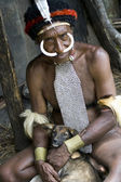 The man of a Papuan tribe in traditional clothes and coloring in — Stok fotoğraf