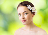Beautiful woman with flowers in her hair and pure skin — Stock Photo