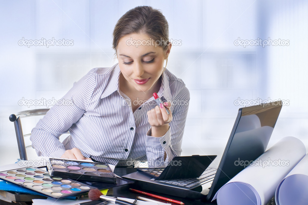 Beautiful businesswoman put make-up  in the office  Stock Photo #7620586