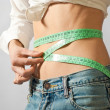 Stock Photo: Girl twisting tape measure over waist