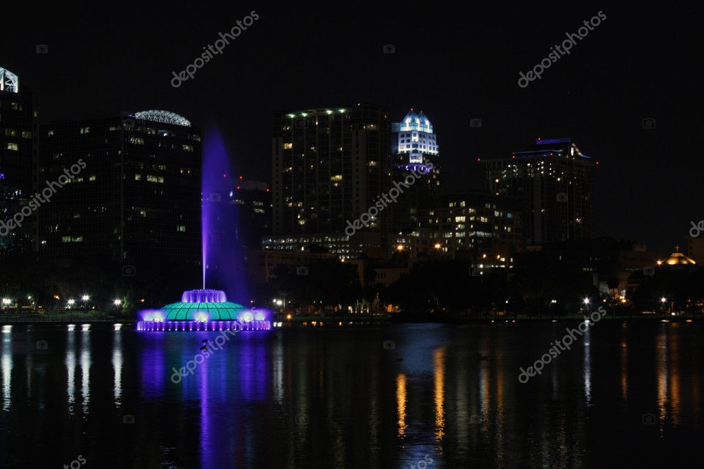 Lake Eola in downtown Orlando, Florida, at night, with the colorful, brightly lit landmark fountain.  Stock Photo #6774818