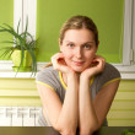 Pregnant woman on kitchen smiles on camera — Stock Photo