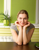 Pregnant woman on kitchen smiles on camera — Stock Photo