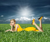 Blonde in yellow dress in green grass — Stock Photo