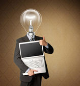 Businessman with lamp-head with open laptop shows welldone — Stock Photo