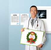 Doctor with empty board with Merry Christmas picture — Stock Photo