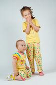 Two cute girls in yellow pajamas — Stock Photo