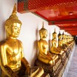 A row of seated Buddhas statue at Wat Pho — Stock Photo