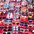 Plastic sunglasses on red table - Stock Photo