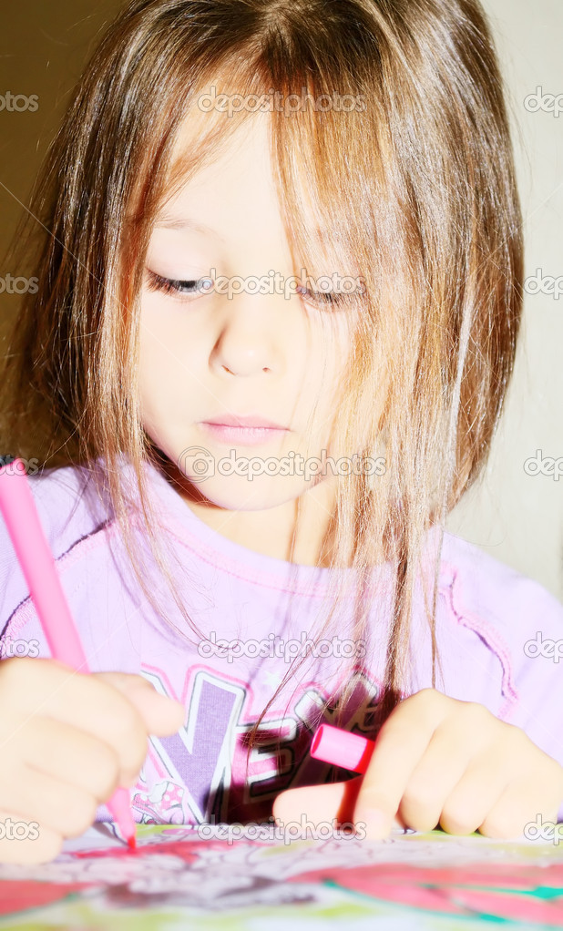 Girl decorates marker drawings in the book — Stock Photo #7072818