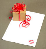 Gift and letter with kiss — Stock Photo