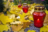 Red votive candle on graveyrd — Stock Photo