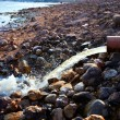 Stream flowing from a pipe on rocks in spring — Stock Photo