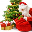 Stock Photo: Santa putting the gift boxes under the Christmas tree