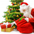 Santa putting the gift boxes under the Christmas tree — Stock Photo
