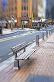 A lens blurred photo of an urban bench — Stock Photo