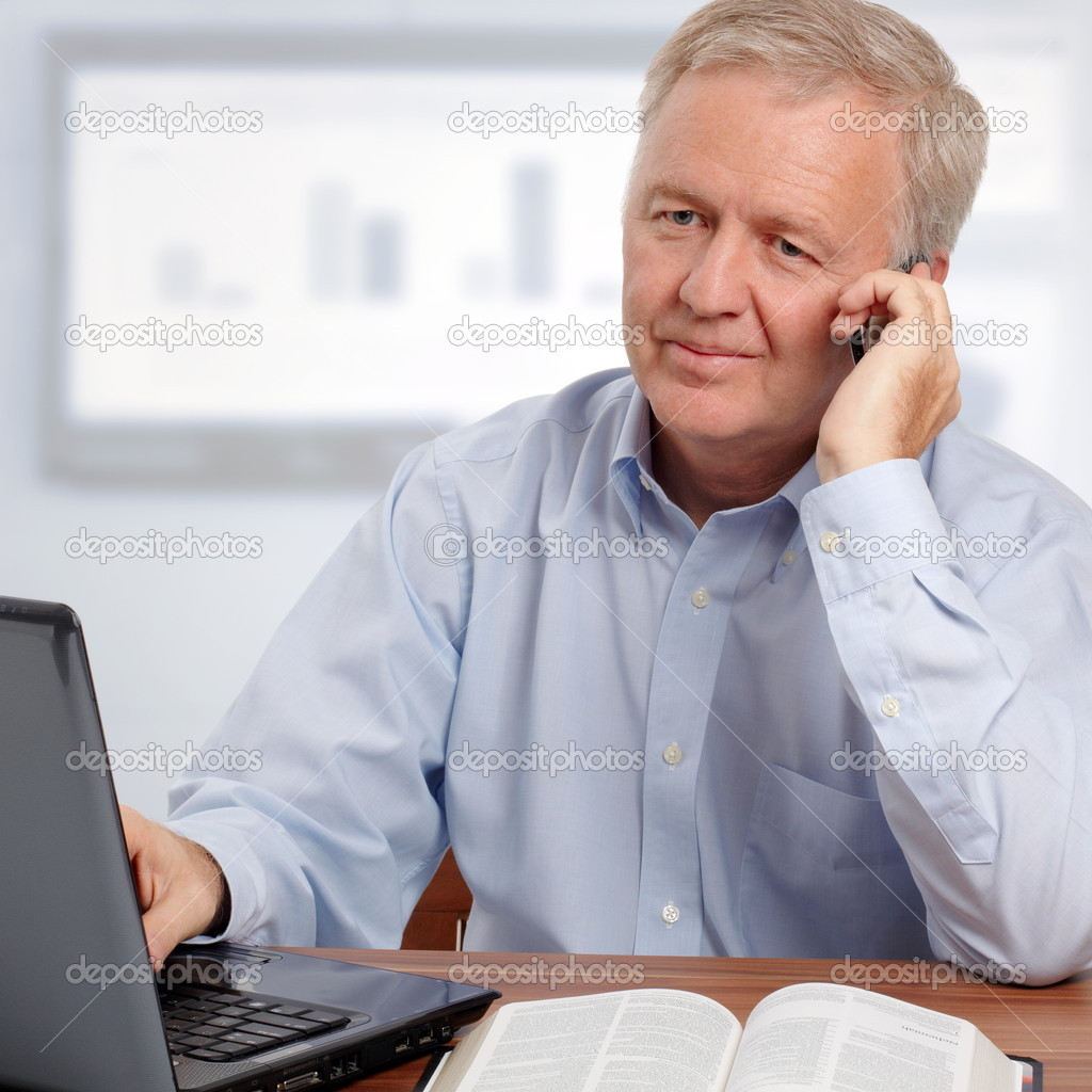 Man talking on phone and smiling in front of the laptop and the Bible — Stock Photo #7140306