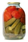 In a glass jar marinaded cucumbers and tomatoes — Stock Photo
