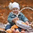 Little girl sits with a basket of apples — Stock Photo #7319906