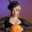 Portrait of a young witch holding a pumpkin — Stock Photo #7639573