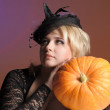 Portrait of a young witch holding a pumpkin — Stock Photo
