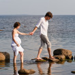 Young romantic pair walks at water — Stock Photo
