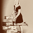 Young woman and a lot of old suitcases - Lizenzfreies Foto