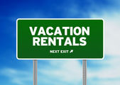 Green Road Sign - Vacation Rentals — Stock Photo
