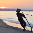 Silhouette of a fisherman on beach at sunrise — Stock Photo #6783221