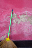 Broom leaning against a grunge pink wall — Stock Photo