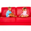 Brother and sister on red sofa — Stock Photo #7445801