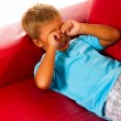 Boy on red sofa — Stock Photo