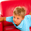 Boy on red sofa — Stock Photo #7485862