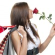 Woman with red rose flower, shopping bags in supermarket — Stock Photo