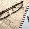 Glasses, pen and notebook laying on newspaper with financial num — Stock Photo #7312502