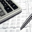 Calculator, steel pen and financial data with graphs. — Stock Photo