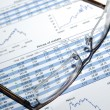 Glasses on printed stock report with graphs and tables. — Stock Photo