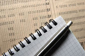 Pen and notebook laying on newspaper with financial data. — Stock Photo