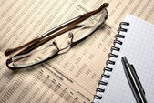 Glasses, pen and notebook laying on newspaper with financial num — Stock Photo