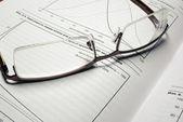óculos deitado no livro com gráficos financeiros. — Foto Stock