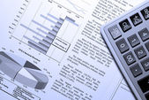 Calculator and stock market report with visual aids. — Stock Photo