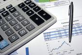 Steel pen, calculator and stock market analysis report. — Stock Photo