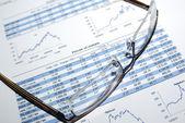 óculos no relatório de estoque impresso com gráficos e tabelas. — Foto Stock