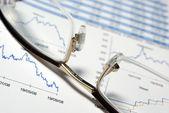 Closeup su bicchieri e la relazione finanziaria con grafici e dati. — Foto Stock