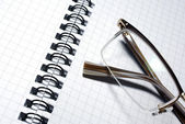 Glasses laying on spiral notebook. Business concept. — Stock Photo