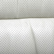High quality perforated beige car leather textured background. — Stock Photo