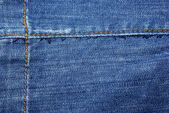 Blue jeans with yellow stitches abstract textile background. — Stock Photo