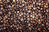 Heap of brown roasted coffee beans as background or backdrop. — Stock Photo